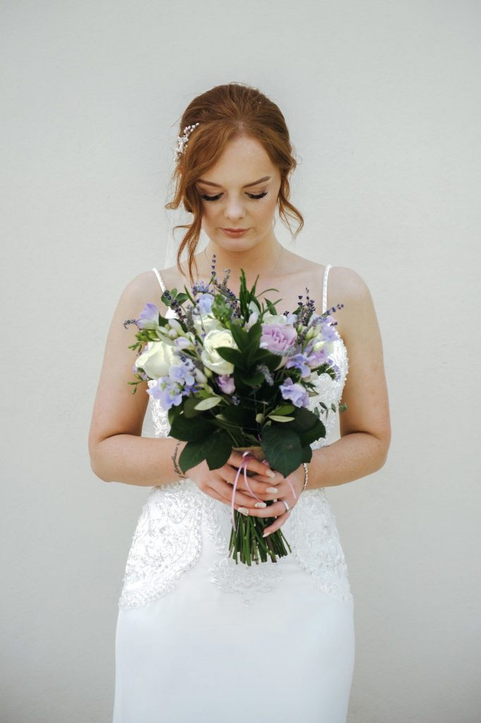 A happy bride holding a beautiful bunch of flowers. Taken by wedding photographer, Lee Hatherall